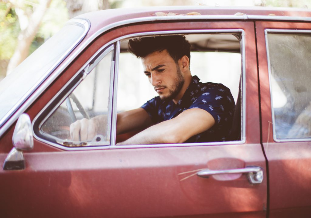man tired inside a car stressed out exhausted and has lots of things on his mind